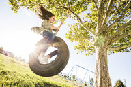 Low angle view of playful girl swinging on tire swing hanging from branch at park during sunny day - CAVF49415