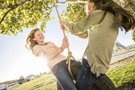 Playful friends swinging on tire swing at park during sunny day - CAVF49418