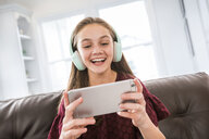 Cheerful girl using headphones and smart phone while sitting on sofa at home - CAVF49424