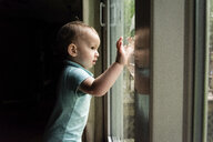 Side view of cute baby boy looking through window while standing in darkroom at home - CAVF49427