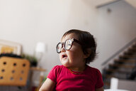 Close-up of cute baby girl wearing eyeglasses while sitting at home - CAVF49445