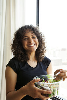 Portrait of happy woman eating salad while standing by window at home - CAVF49451