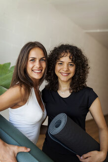 Portrait of female friends carrying exercise mats while standing against wall in yoga studio - CAVF49484