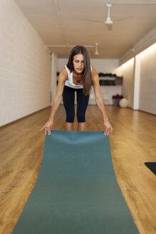 Woman placing exercise mat on hardwood floor in yoga class - CAVF49487