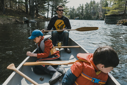 Father and sons canoeing on lake in forest - CAVF49534