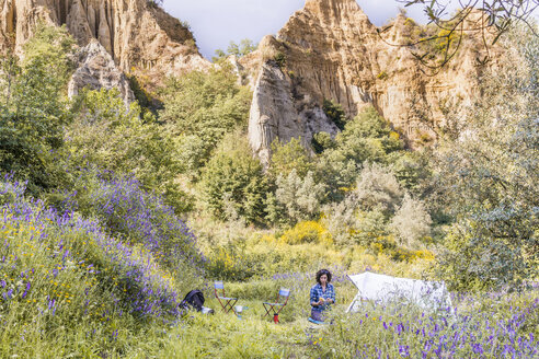 Woman camping on grassy field against rock formations in forest - CAVF49540