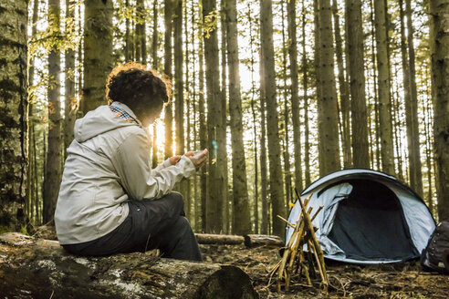 Woman using mobile phone while sitting on log at campsite in forest - CAVF49546
