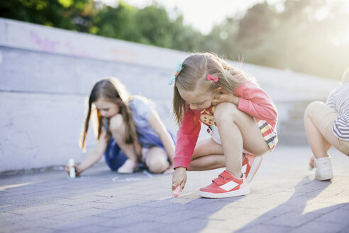 Friends drawing with chalks on street - CAVF49552
