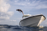 Low angle view of man diving into sea from yacht against cloudy sky - CAVF49588