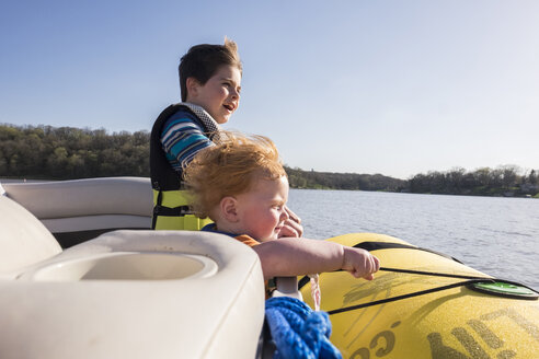 Brothers wearing life jackets while standing in boat on lake against clear sky during sunny day - CAVF49597