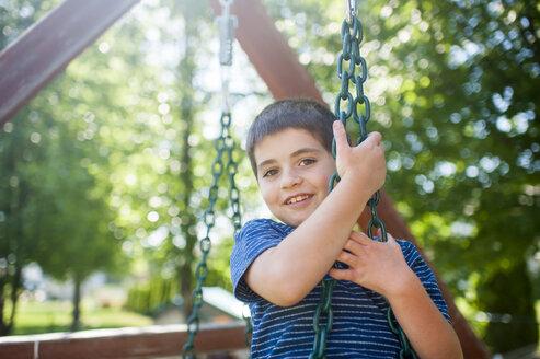Portrait of happy boy swinging against trees at yard - CAVF49603