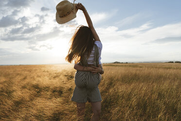 Happy woman carrying twin sister while standing on grassy field against sky during sunset - CAVF49609