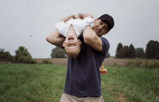 Portrait of happy father picking son upside down while standing on grassy field against sky at park - CAVF49615