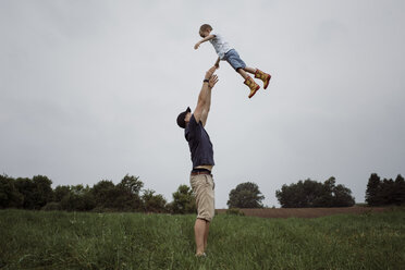Happy father throwing son in air while standing on grassy field against sky at park - CAVF49618