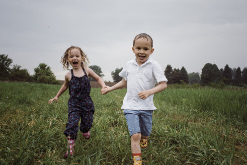 Portrait of happy wet siblings holding hands while running on grassy field against sky at park during rainy season - CAVF49621