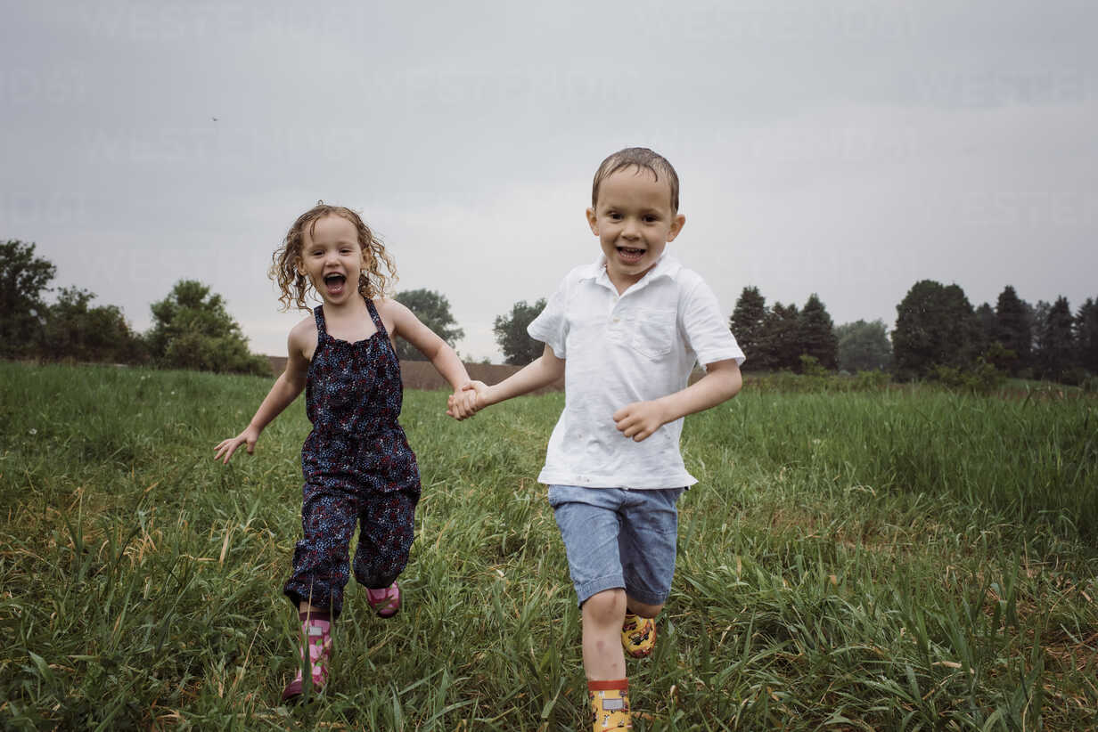 Portrait of happy wet siblings holding hands while running on grassy field against sky at park during rainy season - CAVF49621 - Cavan Images/Westend61