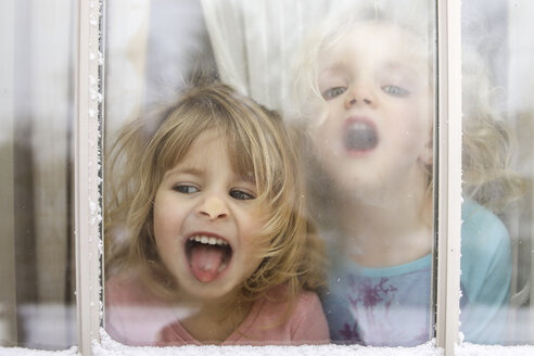Playful sisters in house seen through window during winter - CAVF49633