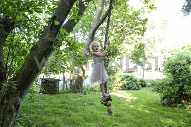 Cute girl looking away while swinging on rope swing at yard - CAVF49636