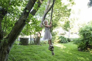 Cute girl looking away while swinging on rope swing at yard - CAVF49636