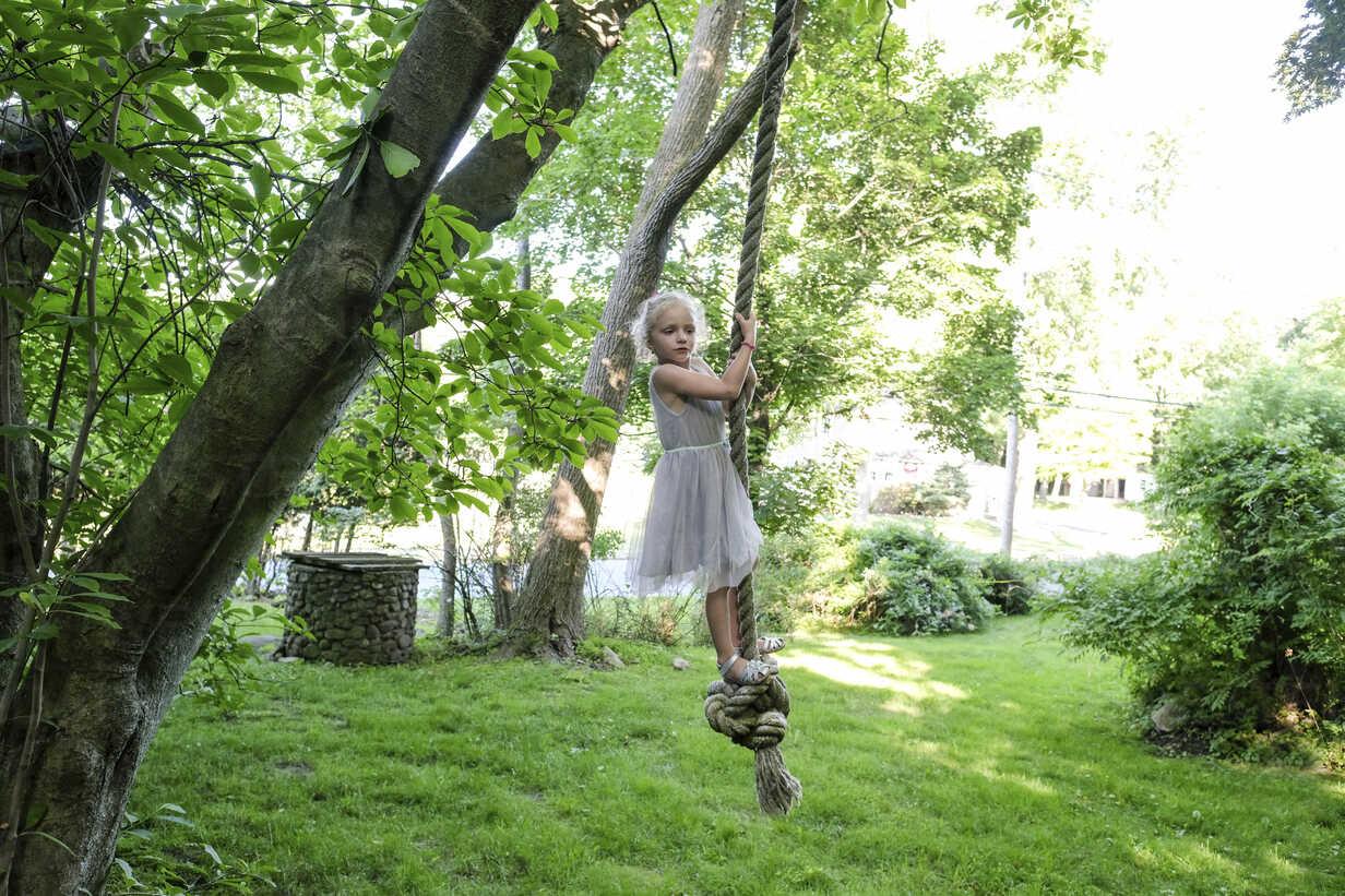 Cute girl looking away while swinging on rope swing at yard - CAVF49636 - Cavan Images/Westend61