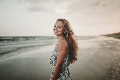 Portrait of happy woman standing at beach against sky during sunset - CAVF49654