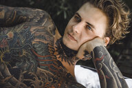 Close-up of thoughtful tattooed man lying on blanket while looking away - CAVF49660
