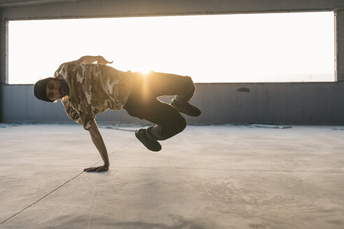 Man doing breakdance in urban concrete building, standing on hand - JRFF01910