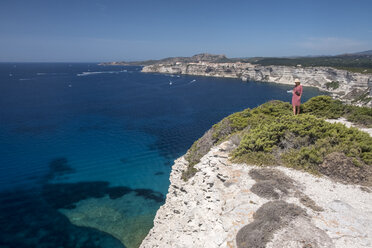 Corsica, Mediterranean coast, woman standing on rocky cliff - HAMF00462