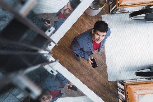 Businessman in lobby of a modern building, using smartphone - KKAF02428