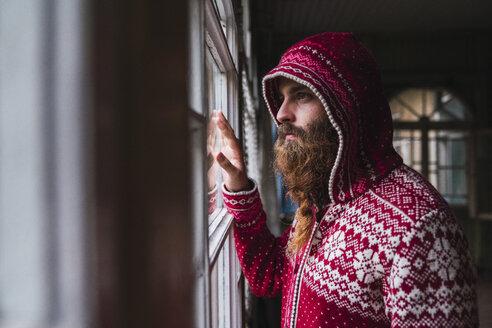 Portrait of pensive man with beard wearing hooded jacket looking out of window - KKAF02450