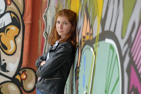 Italy, Finale Ligure, portrait of redheaded teenage girl leaning against mural - LBF02123