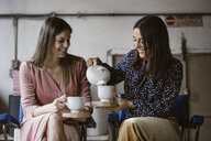 Two friends drinking tea together in a loft - ALBF00645