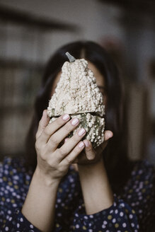 Woman's hands holding sliced white decorative gourd - ALBF00654