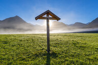 Germany, Bavaria, Allgaeu, Allgaeu Alps, Loretto meadow near Oberstdorf, field cross against morning sun - WGF01262