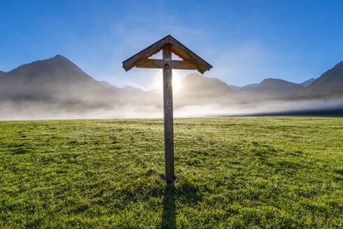 Germany, Bavaria, Allgaeu, Allgaeu Alps, Loretto meadow near Oberstdorf, field cross against morning sun - WGF01262