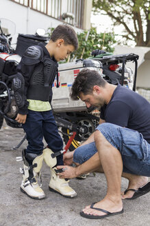 Father preparing son for a motorbike trip - FBAF00121