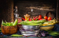 Colorful pea and bean pods on rustic kitchen table - INGF02274