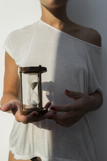 Young woman holding an hourglass at sunset against white wall - JPTF00028