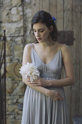 Young woman wearing grey dress holding a flower - ALBF00669