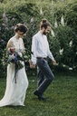 Bride and groom walking hand in hand on meadow - ALBF00687