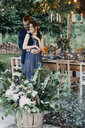 Happy bride and groom embracing at festive laid table outdoors - ALBF00693
