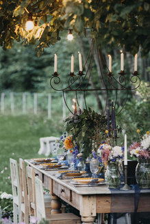 Festive laid table with candles under a tree - ALBF00696
