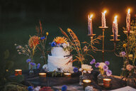 Wedding cake on table with candles outdoors - ALBF00705