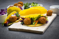 Sweet potato falafel in taco shells, with red cabbage, salad, carrot, yogurt sauce and black sesame - LVF07479