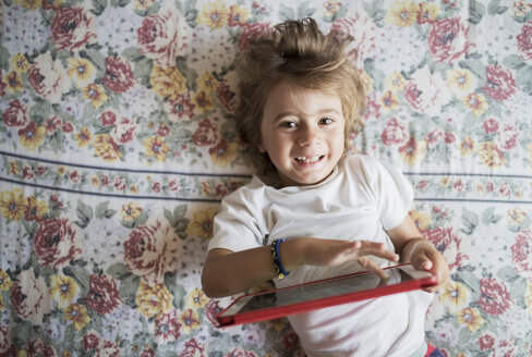 Portrait of happy little boy lying on bed with digital tablet - AZOF00082
