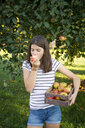 Girl eating freshly harvested apple - LVF07483