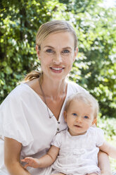 Portrait of smiling mother holding her baby girl outdoors - TCF05886