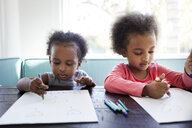 Sisters drawing with crayons on papers at home - CAVF49678