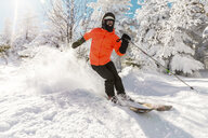Full length of young man skiing on snow against trees during winter - CAVF49693