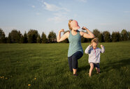 Mother with daughter exercising on grassy field at park against sky during sunset - CAVF49720